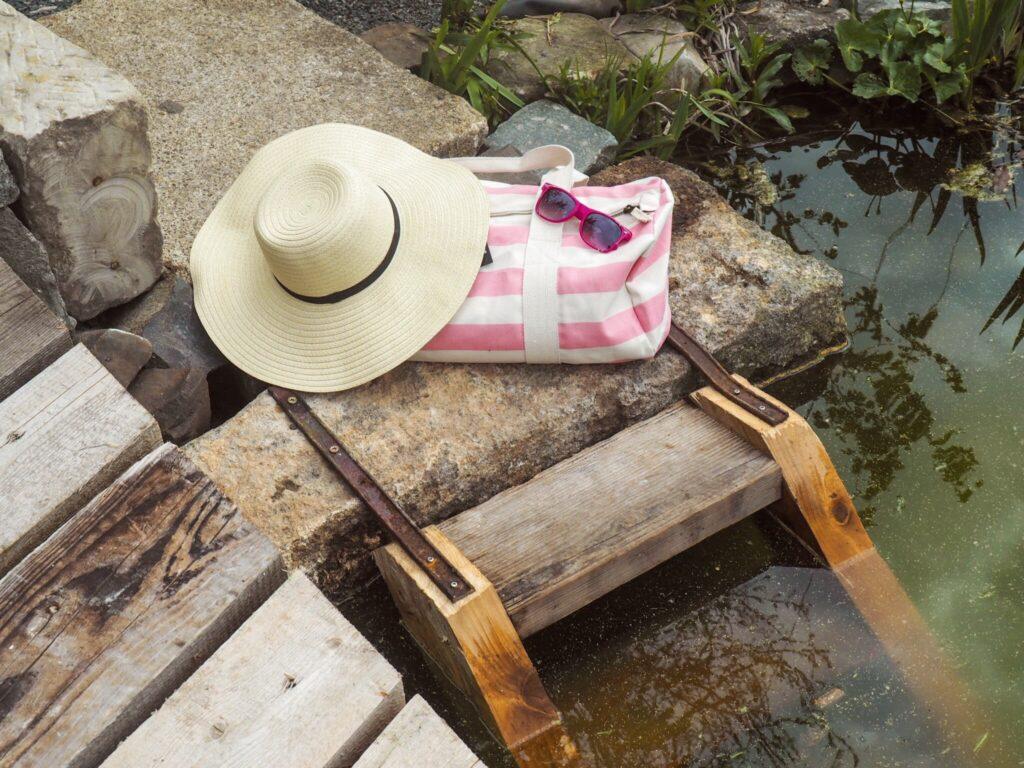 Dámský klobouk a růžová barelová taška u vody
